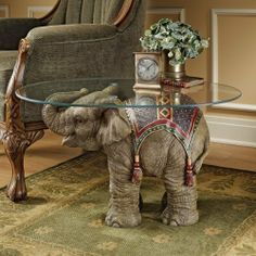 """Indian Elephant Sculptural Table by Artistic Solutions. $271.62. Your home will reflect the exotic styling of Holi, the much-anticipated festival where Indian elephants, attired in embroidered velvet drapes and glittering tassels, lift their trunks as a symbol of good fortune to the coming year. Shown to full advantage beneath a 30""""-long, 3/8""""-thick glass top, our sculptural beast of kings is cast in quality designer resin to capture each detail, and then exquisitely hand-pai..."""