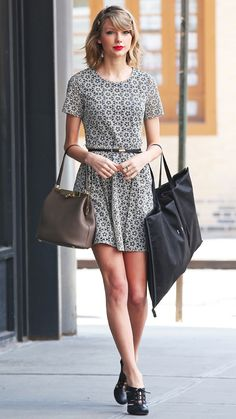 Taylor Swift in a black-and-white color scheme (except for her taupe Dolce & Gabbana bag) with a belted print dress and black lace-ups.
