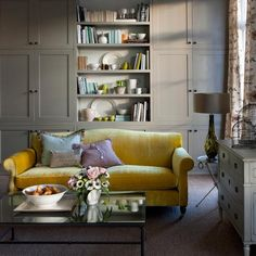 Built in cupboards are a great practical solution for family living rooms. Add bookshelves and colourful accessories to liven up the space and for that extra bit of zing, add a beautiful bright sofa.