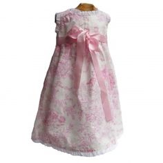 Espectacular faldón de Toile de Jouy largo en rosa y blanco para bebé. Volantitos blancos en cuello y bocamanga. Lazo de raso en la cintura. Talla única para bebés de 0-6 meses. 100% algodón.