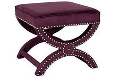 Gleaming nickel nail heads accentuate the curved legs of this curule-style ottoman.