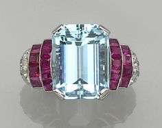 An aquamarine, ruby, diamond and platinum ring  centering an emerald-cut aquamarine, flanked by square-cut rubies, with old European-cut diamond shoulders. Retro or Retro style.