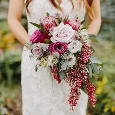 Cascading berries add an unexpected element to this jewel-toned rose bouquet.