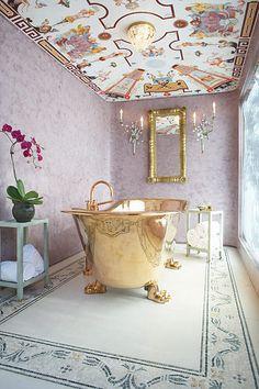 Gold bathtub in a lavendar bathroom.  Fabulous ceiling.