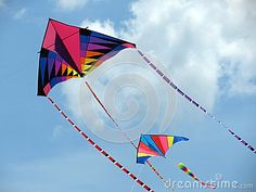 Two brightly coloured kites soar up to the clouds on a summer's day.
