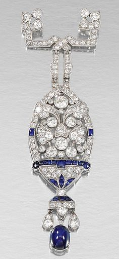 SAPPHIRE AND DIAMOND BROOCH, CIRCA 1915.  Of open work stylised floral and foliate design, millegrain-set with single- and circular-cut diamonds embellished with buff-top sapphires and suspending a cabochon sapphire drop, maker's marks.