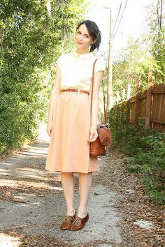 belted dress with peter pan collar, brown oxfords and brown purse. cute nerdy glasses optional.