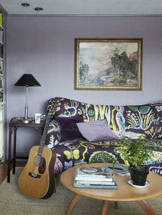 purple couch + funky pattern + wood table + light rug