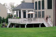 Pressure treated and painted deck with custom rail design, custom trim around deck and support posts with stairs stepping down to a gorgeous patio with outdoor fireplace.