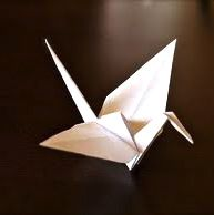 Folded paper crane - one of many on following pictured mobile with thousands of cranes, each carrying a prayer of peace.