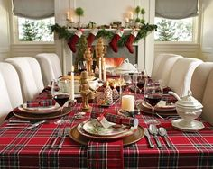 love love love.  tablecloth, table settings,  serve ware, white upholstered chairs, fire, garland, stockings, and nutcrackers