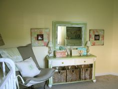 I love the wicker baskets and the distressed gree mirror. a pale green and yellow nursery is wonderful :)