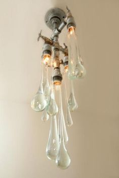 A beautiful and unusual chandelier  -  The installations come in all shapes and sizes, from rigs containing multiple bulbs, to more simple, single bulb lamps as seen below, reflecting the calm tranquility of growing drops of water. However, with Liquid Light the drops never quite fall!