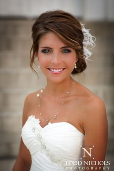 Pretty updo for your wedding, except without the feather thingy. Her dress is pretty too.: