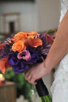 The bride is carrying puple fuji mums, purple and tangerine calla lilies, burnt orange roses, and dark purple lisianthus
