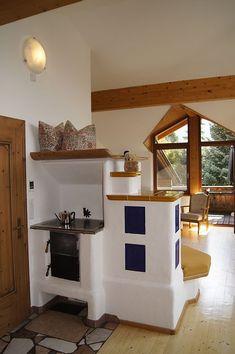 Ferienwohnung Spielmann Ehrwald  - hohes Wohnzimmer mit Sichtdachstuhl und gemütlichem Kachelofen