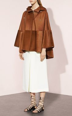 This hooded **Prabal Gurung** cape features a leather construction with Kangaroo fur details and front slash pockets.