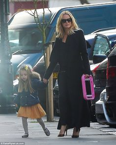Leggy lady!Wrapping up in a long black duster coat, Amanda, 45, looked effortlessly chic on the outing, slipping her slim pins into a pair of skinny jeans as she held hands with her youngest daughter, Hollie