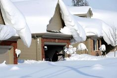 Snowdrifts create a beautiful setting as a man tries to dig out his driveway on Bowen Rd in Lancaster, N.Y. Wednesday, Nov. 19, 2014. A lake-effect snow storm dumped over five feet of snow in areas across Western New York. Another two to three feet of snow is expected in the area, bringing snow totals to over 100 inches, almost a years' worth of snow in three days.