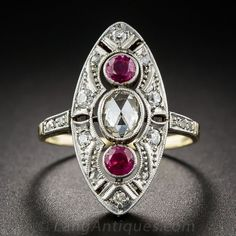 Vintage Diamond and Ruby Dinner Ring. Expertly handcrafted during the early twentieth-century in platinum over gold, this transitional Edwardian/Art Deco dinner ring measures 7/8 inch and centers on a glistening foil-backed rose-cut diamond, accompanied top and bottom by a pair of vibrant red rubies. The three stones are bezel-set and float atop a classic navette-shape dome, studded with small round diamonds and accentuated with delicate pierced and milgrain details...