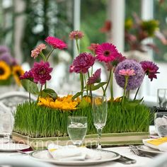 Long-stemmed flowers set into rows of wheatgrass look as though they are growing right out of the centerpieces.