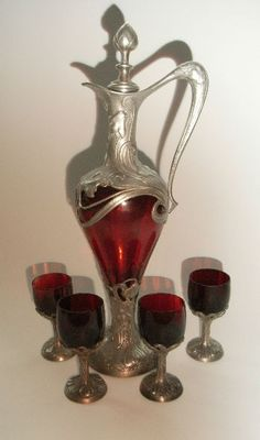 German Pewter and Ruby Glass    Art Nouveau German decanter set with four glasses, c1900.