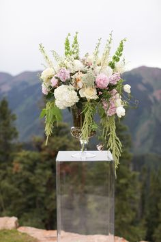 Tall pink and white altar arrangement by Mountain Flowers of Aspen featuring white hydrangea, white peonies, pink roses on clear lucite pedestal. #aspen #wedding #weddingdeck