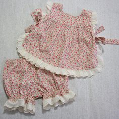 Cute baby & toddler sewing pattern. The Isabelle Baby Set is a lovely little outfit with a tabbard style top and matching bloomers or long pants. It can be adapted to all seasons. There are three versions included in the pattern and sewing tutorial.  DESCRIPTION: The top is a tabard style with open sides held together with bow ties. The back yoke is open and has a button and loop closure. It can be trimmed with either lace or bias binding. The bloomers are pull-on with an elastic waist and…