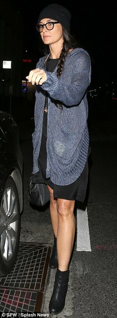 Boho chic: The 50-year-old wore a black dress and over-sized cardigan paired with black booties