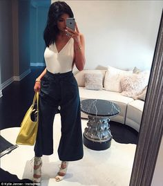 Quirky style: Kylie snapped a selfie of her revealing top and cropped trousers before head...