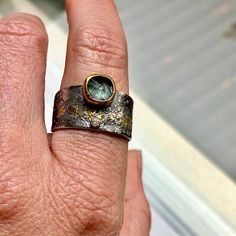 A dusty pale blue aquamarine ring! This little aquamarine has a rainbow in it!! The band is incredibly comfortable and has a beautiful reticulated pattern with 3 different types of silver fused together with bits of gold. This ring is about a 8 but can be really easily sized up or