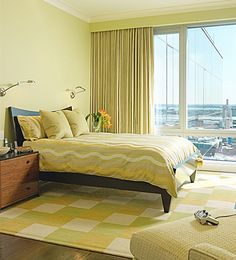 A sunny bedroom is made so with custom bedding and custom area rug in bright colors and playful patterns.