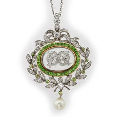 A turn of the century green demantoid garnet and diamond pendant, the rock crystal centre with applied diamond motif surrounded by calibré-cut demantoid garnets, within a diamond and demantoid laurel wreath and bow, circa 1900.