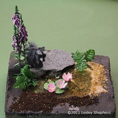 A finished miniature pond made from E-Z Water in dolls house scale is set into a foam base ready to be completely landscaped.