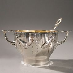 This is not contemporary - image from a gallery of vintage and/or antique objects. A French Art Nouveau silver bowl by Antoine Cardeilhac, featuring a mistletoe motif, with matching spoon.