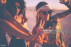 Three girls dancing and making hand gestures at a summer beachparty at sunset