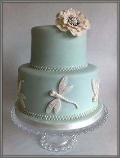 """""""Nicola""""  : 2 Tier Cake in pale duck egg blue with ivory royal icing pearls.  Bottom tier is decorated with sugar paste dragonflies and top tier has an ivory bloom.    6"""" & 8""""   Price £265"""
