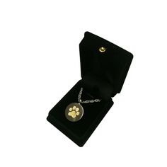 The Dog Paw Print Cremation Pendant is stainless steel and a wonderful memorial for you beloved pet. This pendant features a wonderful two toned silver and gold face with a paw and is designed to contain a small portion of cremains (ashes) in an internal chamber that is secured with a threaded stopper and can be sealed with adhesive.
