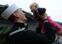 NORFOLK (Nov. 7, 2013) Electricians Mate 2nd Class Joe Gerolmo holds his daughter for the first time during a homecoming celebration for the amphibious assault ship USS Kearsarge (LHD 3) at Naval Station Norfolk. Kearsarge completed an eight-month deployment as part of the Kearsarge Amphibious Ready Group in support of maritime security operations and theater security cooperation efforts in the U.S. 5th and 6th Fleet areas of responsibility.  (USN Comm Spec 1st Class Rafael Martie)