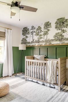 A baby boy nursery gets a woodland themed makeover with deep green, cozy lighting, and peel & stick watercolor style wall mural on a budget.