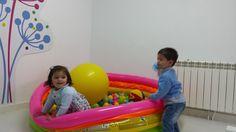 Aydee y Jacobo (alrededor de los 2 años) juegan a entrar y salir de la piscina de bolas como parte de los ejercicios del circuito de psicomotricidad gruesa.