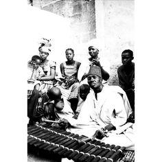 """Opera scattata in una strada di un villaggio nigeriano. L'attenzione è catalizzata sugli """"anonimi"""", considerati più interessanti, più """"degni di essere fotografati"""". Il reportage, dell'agenzia """"D.F.P."""" di Dani Maria Turriccia, si distingue per il suo forte contrasto chiaroscurale, che accresce l'impatto emotivo. Africa, Nigeria 1975."""