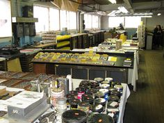 photo  Letterpress Things Chicopee MA    the Kelsey table in the foreground. then 2 slant-tops of symbols, @ signs, etc. followed by a table of letterpress books and manuals, then a table with tympan, brayers and misc., then a table of pressboard, ink, furniture, pica poles, composing sticks, composing stones, brass & copper thins and quads and spacers and past that all the type