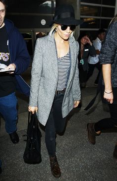 Sienna Miller goes casual at the airport in a striped tee, black fedora and chunky leopard boots