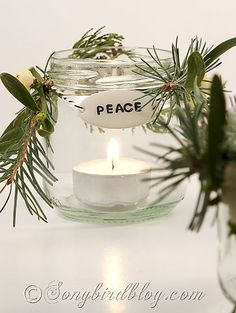 Decorate little glass jars with evergreens and tiny Christmas balls and tags and create a lovely candle holder. See more details at http://www.songbirdblog.com