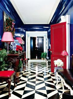 A gracious entry of a New York apartment with high gloss cobalt blue walls, red upholstered leather door and black and white marble floor.