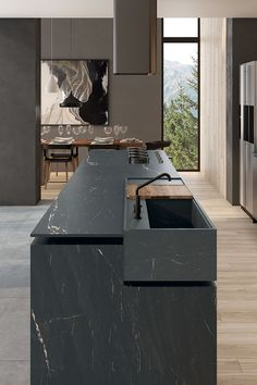 Minotticucine London's sweeping SEVEN metre-long island in timeless Carrara Arabescato marble finishes with a dramatic 60mm-thick cantilevered bar, which covers the hob and slides out to form a sociable hub. | #cosykitchen #darkitchen #blackkitchen #marblekitchen #kitchenisland #homedesign #interiorinspo #renovation #homedecorideas #dreamhome #homeremodel #interiordesign #kitcheninspo #dreamkitchen #kitchendecor #storageideas #stoarge #kitchenstorage #kbbmag