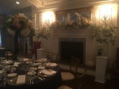 Wedding mantle design over fireplace. Cylinder vases with floating candles votive candles fresh flower designs of ivory hydrangea café au lait dahlias blush cabbage roses and silver dollar eucalyptus.