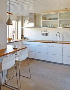 White kitchen cabinets, timber floor, wooden countertop