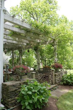 Semi enclosed patio with dry stacked walls, pergola with shading green vegetation
